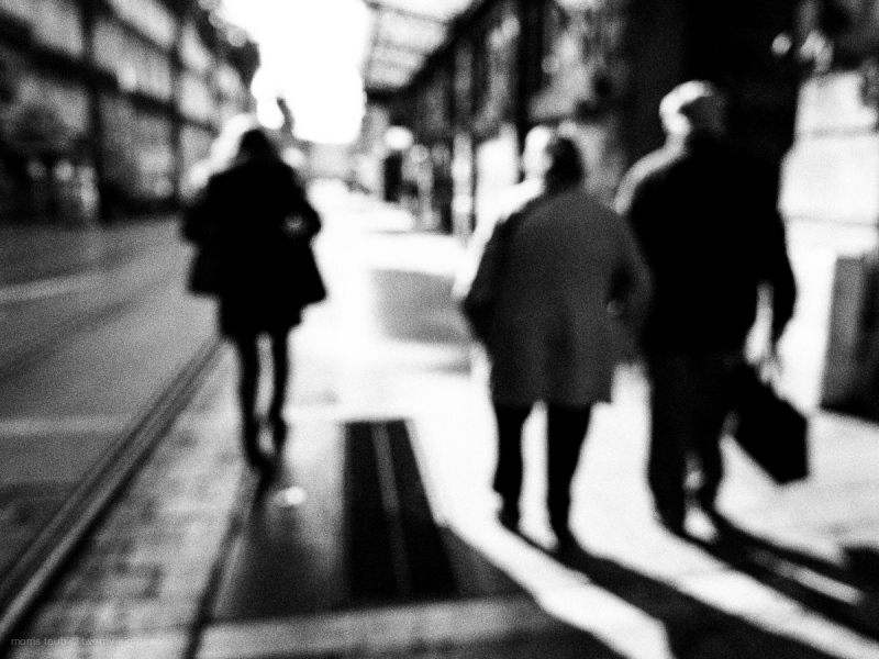 People walking blurred in black and white sun.