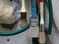 Paint brushes hanging. Garden hose. Green.