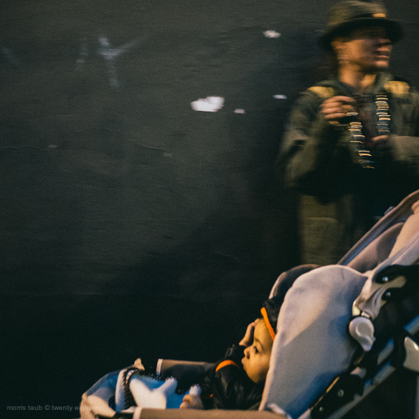 Baby in stroller passing man on street at night.