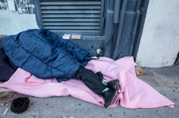 Homeless man sleeping on the sidewalk.