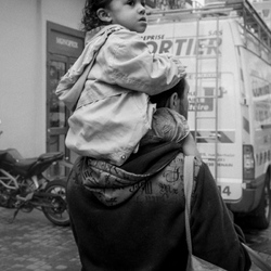 Child riding on his dad's shoulders. B&W.