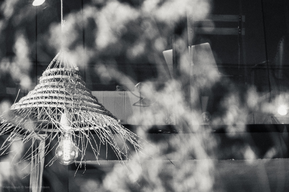 Straw lamp and blurred flowers in restaurant.