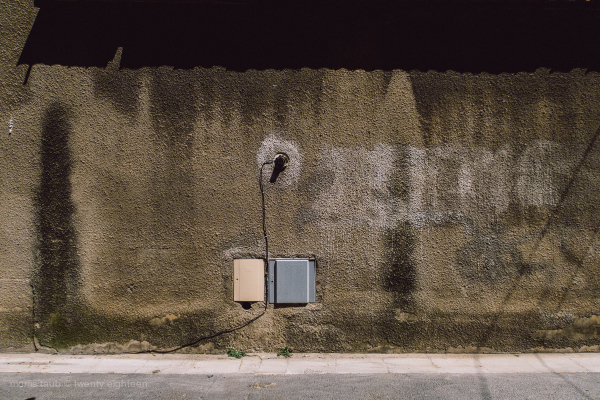 A wall with wires, stains, street, plants.