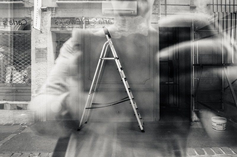 Ladder in store with window reflection.