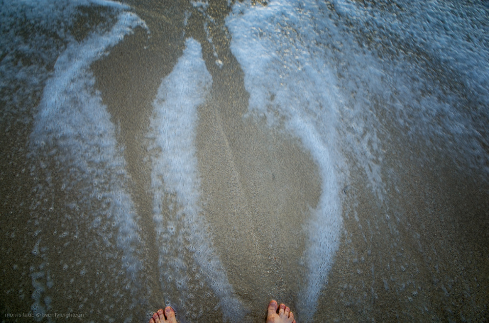 Ocean water swirling around toes. Florida.