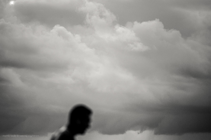 Man walking on the beach with clouds.