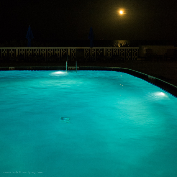 Pool and moonlit ocean at night.