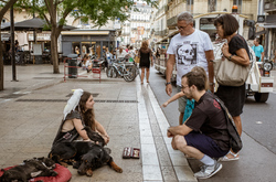 Young girl with birds and dogs sitting in street.