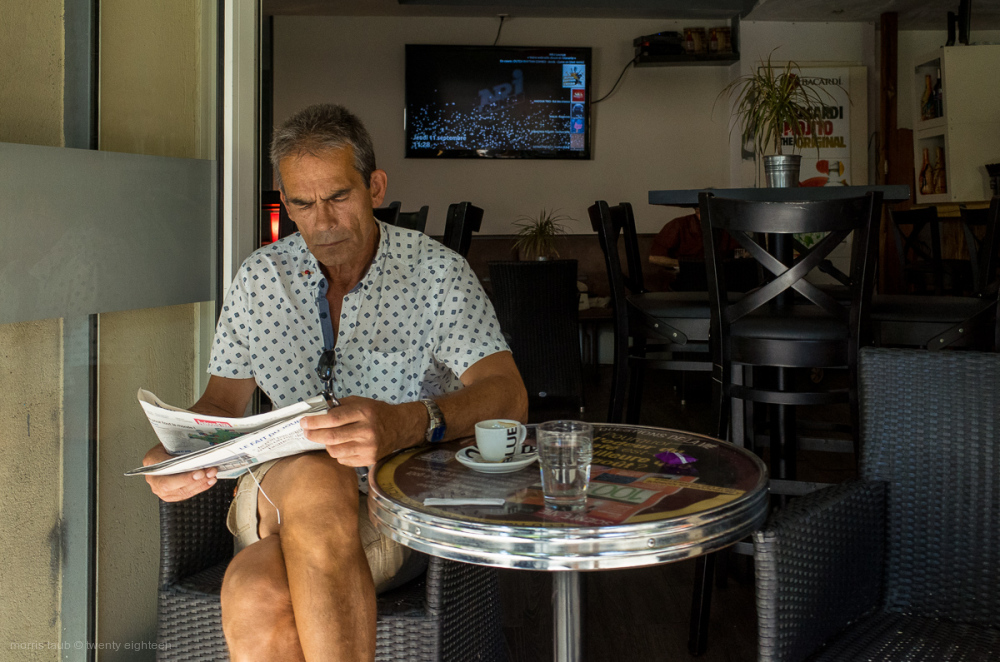 Man reading newspaper with his morning coffee.