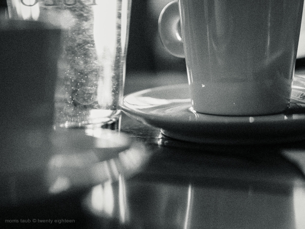 Cafe table top with mug glass coffee. B&w.