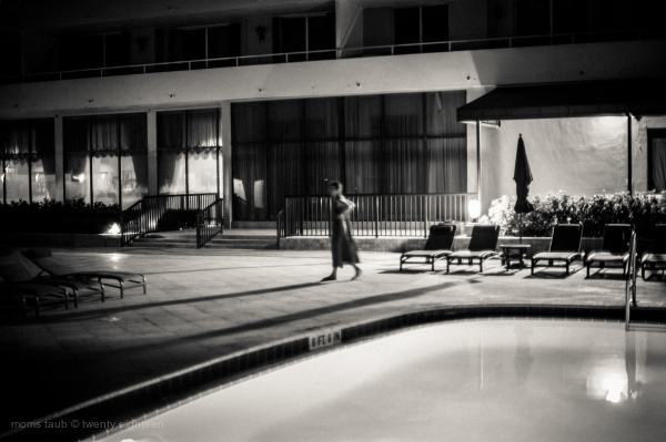 Woman walking by the pool at night.
