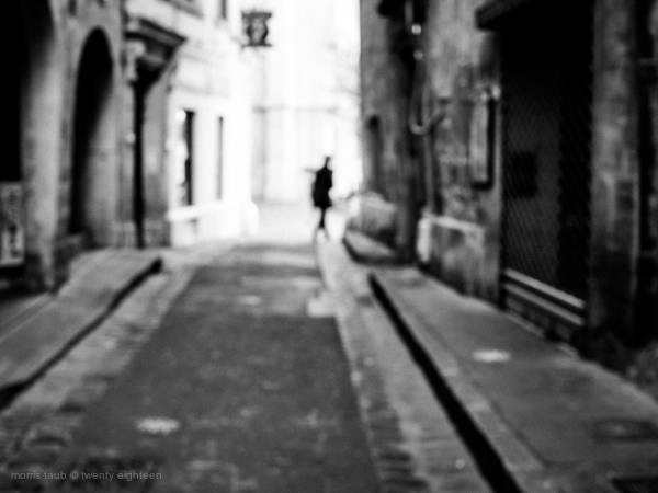 Blurred old french city street with person.