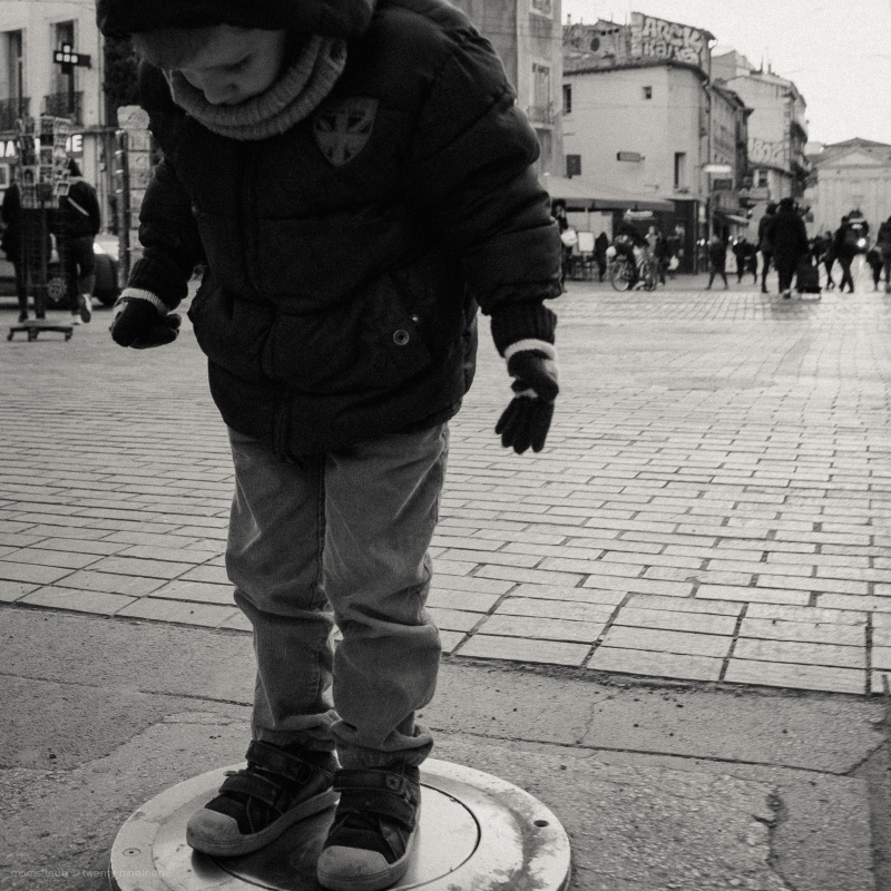Boy standing on street pillar that rises.