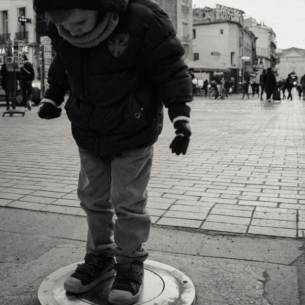 Boy standing on street pillar that rises.