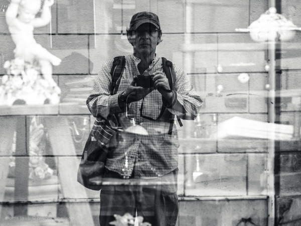 Self-portriat in store window. Black and white.