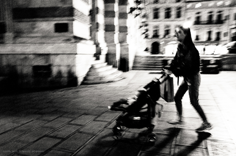 Mother running with her baby in stroller. B&W.