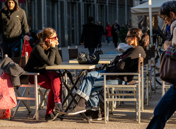 Two women talking at outdoor cafe.