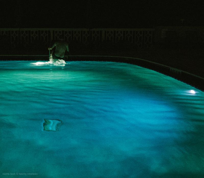 Man leaving blue pool at night. Miami Beach. 2016.