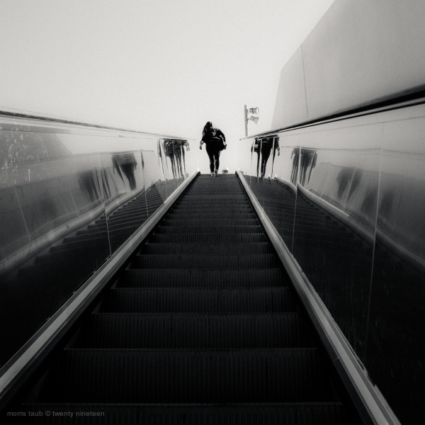 Woman headed up escalator.