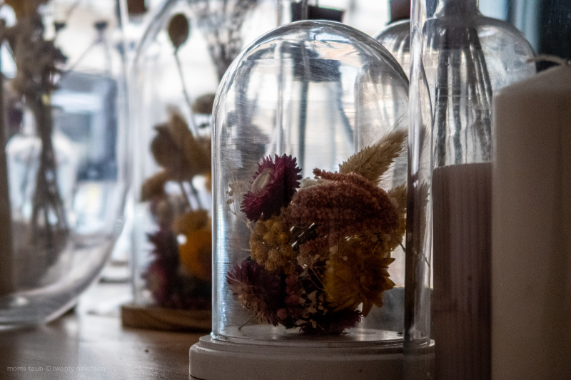 Table with dead flowers under glass at restaurant.