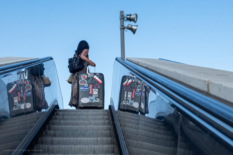 Woman headed up escalator into train station.