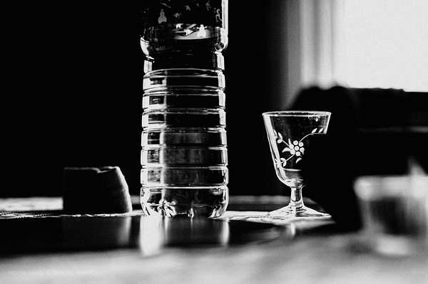 Bottled water and glass on table. Black and white.