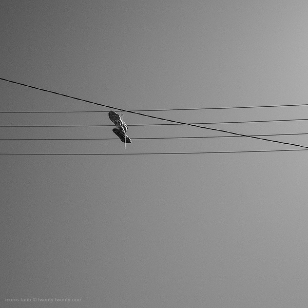 Sneakers hanging by laces high on phone wire.