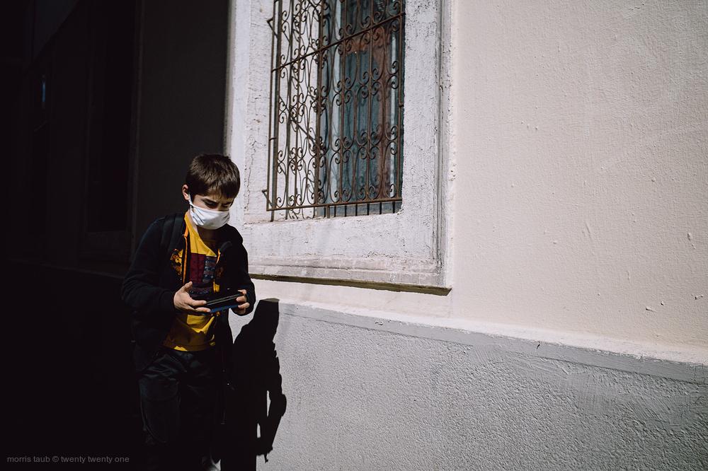 Boy immersed in smart phone walking on the street.