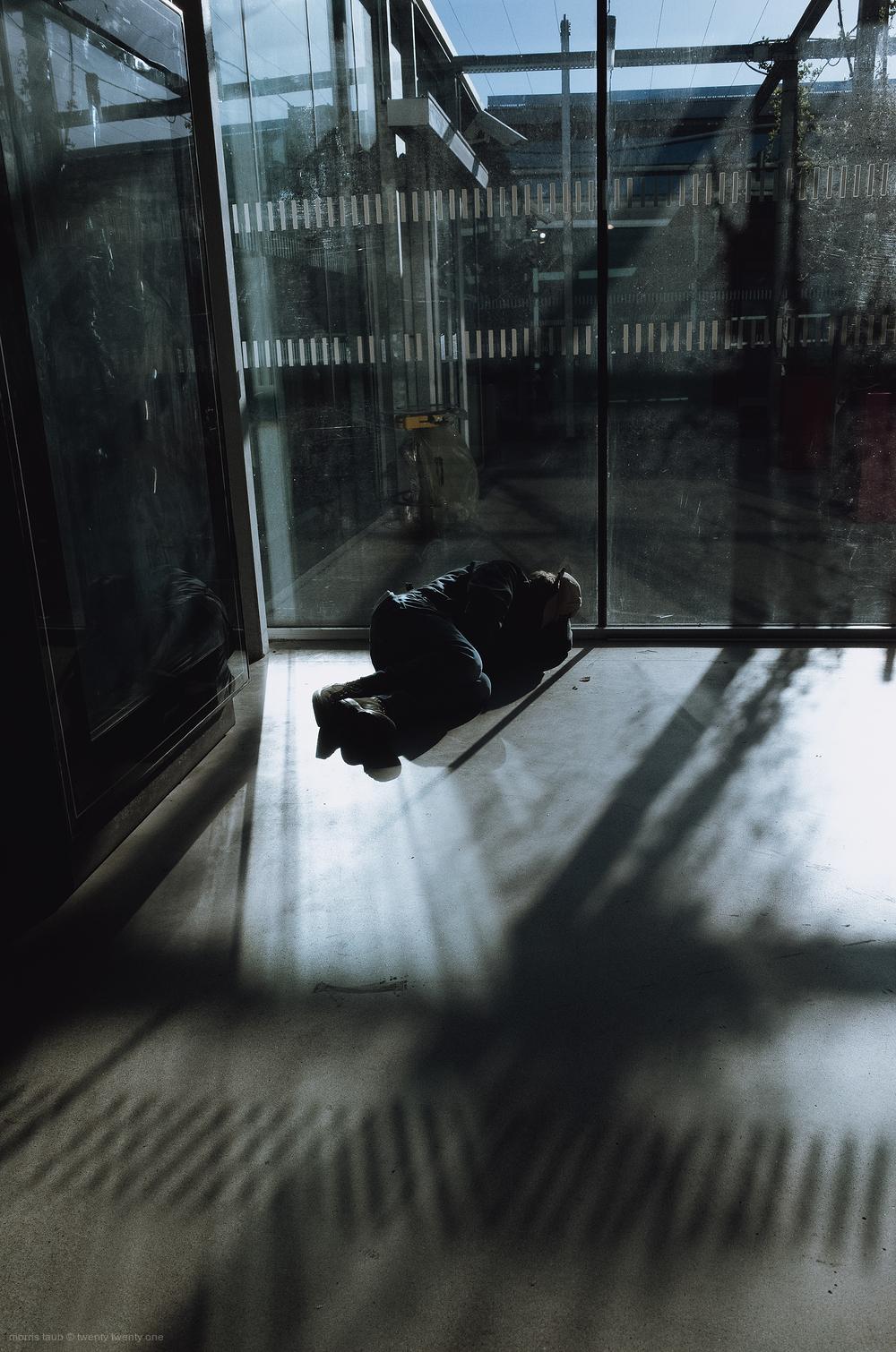 Man sleeping on floor in train station.