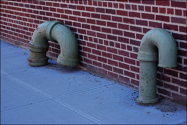 Two pipes against a brick wall in NYC