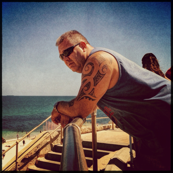 man rests on a rail at the beach