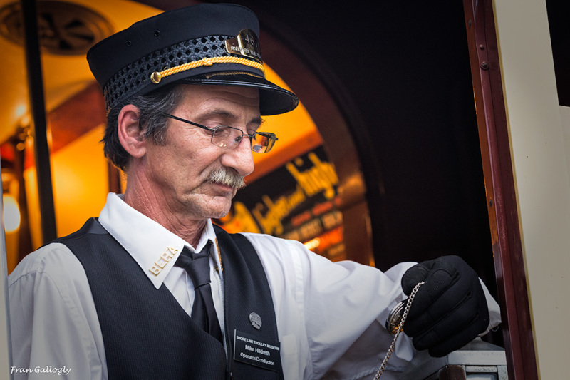 Trolley conductor checks his watch and time table