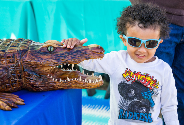 Child with Carved Alligator at the Farmers Market