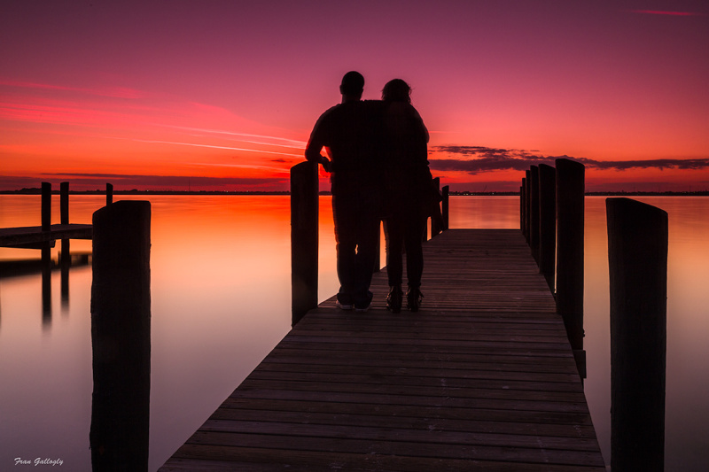 Lovers on a pier at sunset , hutchinson island, FL