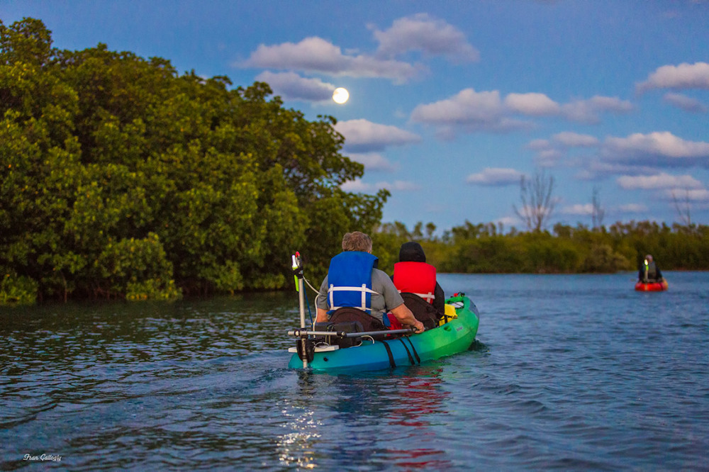 Kayaks under a full moon on hutchinson island, fl