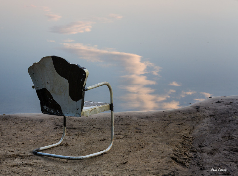 Chair on beach with cloud reflections