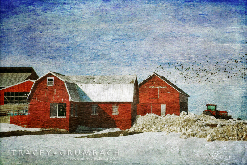 snow over a rural barn with tractor in distance