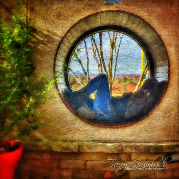 girl lying in a circular window looking out at