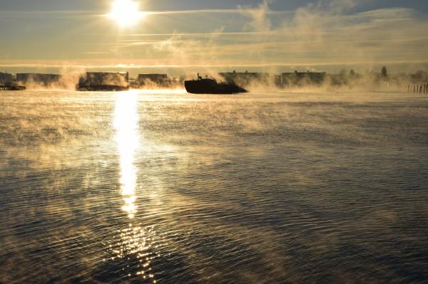 sea smoke rises around a pier in Portland Maine