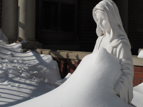 Snow surrounds statue of Virgin Mary