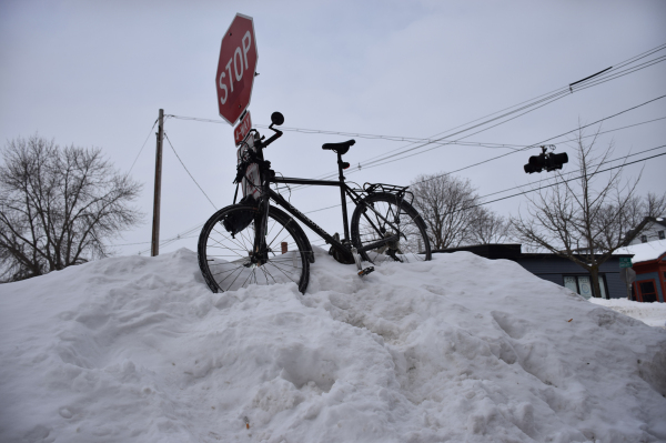 bicycle parked atop a snow mound