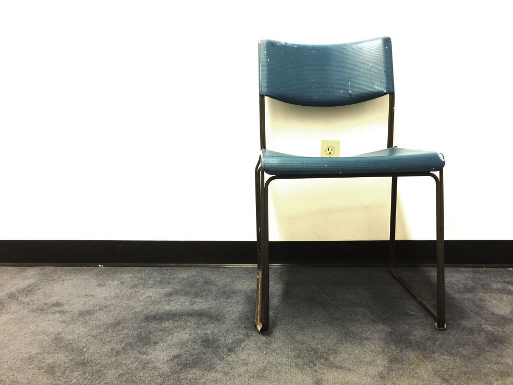 a blue chair in front of white wall and plug