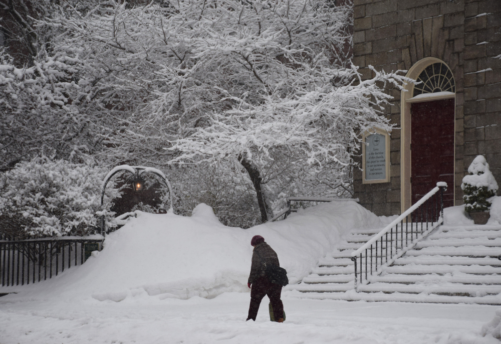 Woman walks in snow in front of church's red door
