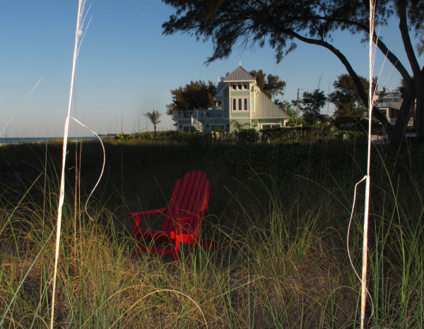 a red chair sits in sea grass on beach in Florida