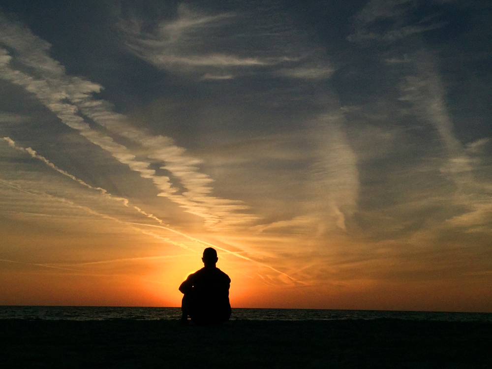 man sits on Florida beach watching sun set