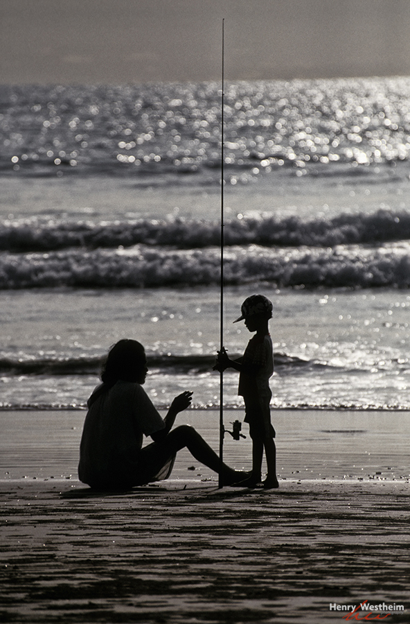 Father teaching his son to fish.