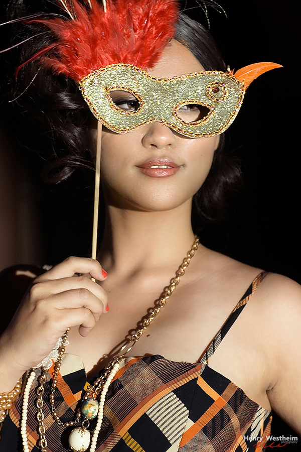 Young Asian woman holding a masquerade mask