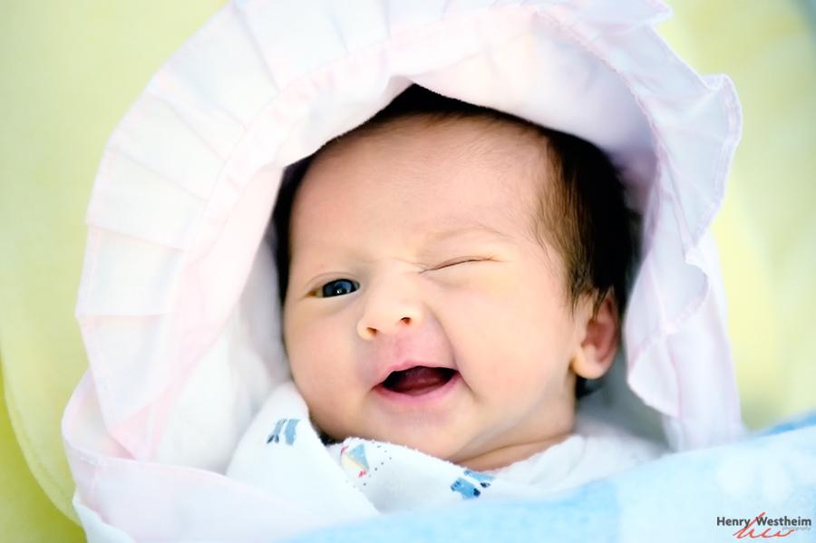 Portrait of a 1 week old newborn baby girl winking