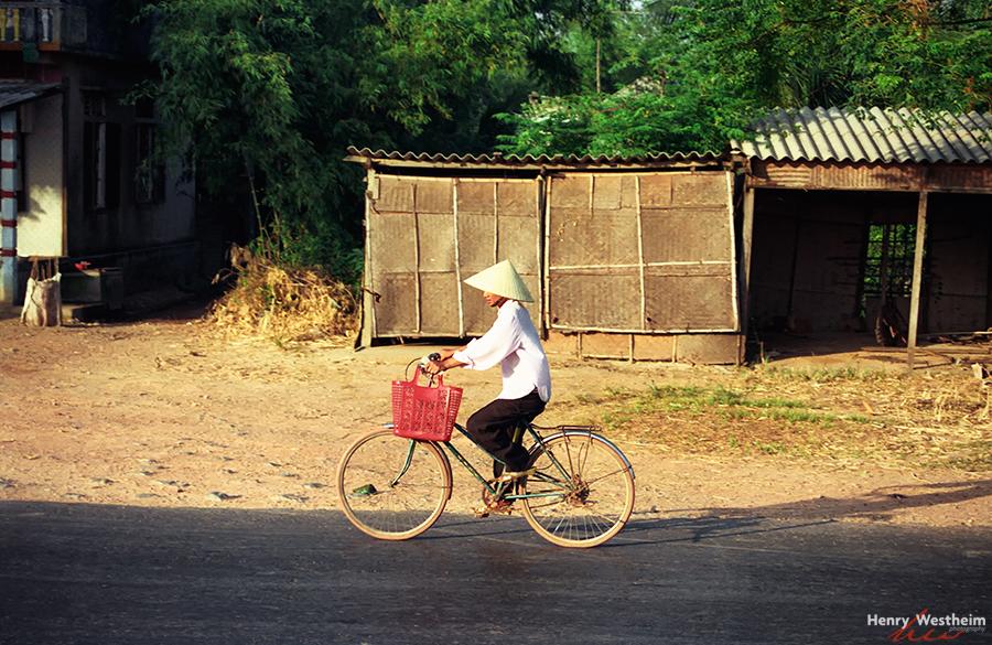 Vietnam, Hue.  Vietnamese woman riding a bicycle.