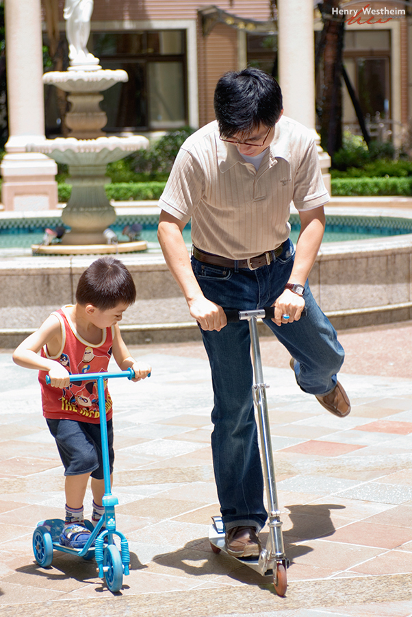 Asian father teaching his son to ride a scooter